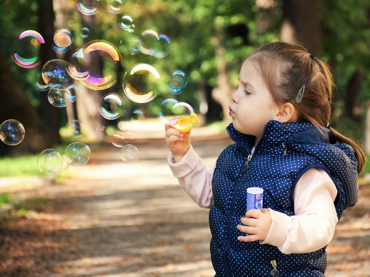 Kind Mädchen spielt mit Seifenblasen