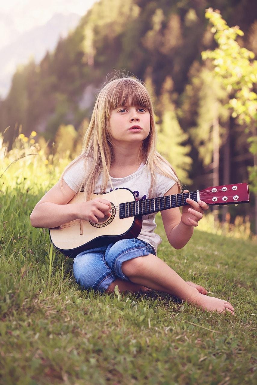 Kind spielt mit Gitarre Musik